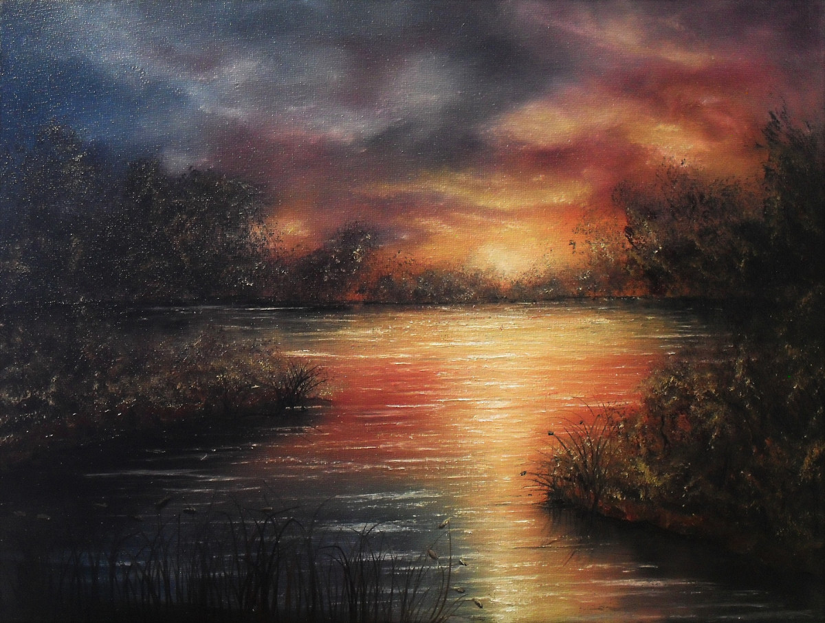 Blush of Nightfall. Colourful oil painting of a lake at sunset. The clouds are blue red and yellow. The colours are reflecting in the water. You can see some bushes and trees on a few islands. Canvas 40x30cm. by Lia van Elffenbrinck